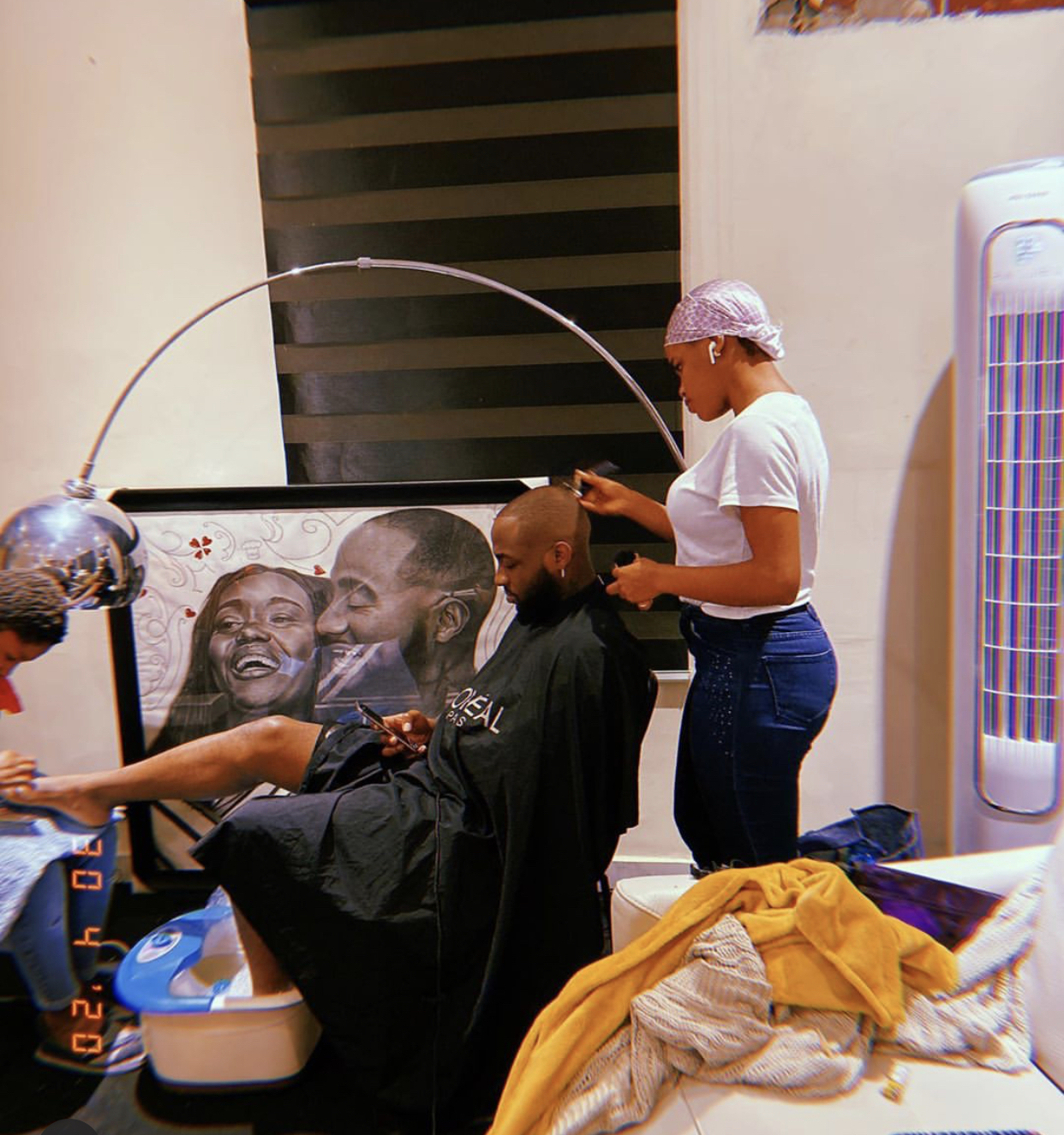 Nigerian singer, Davido getting a haircut done by a female barber